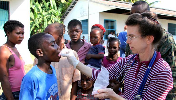 Aid providing medicine to a child in Haiti