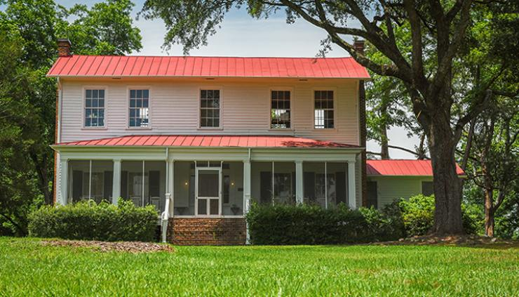 Flannery O'Connor's Andalusia: a two-story plantation plain style home. It is painted white wih a red metal roof.