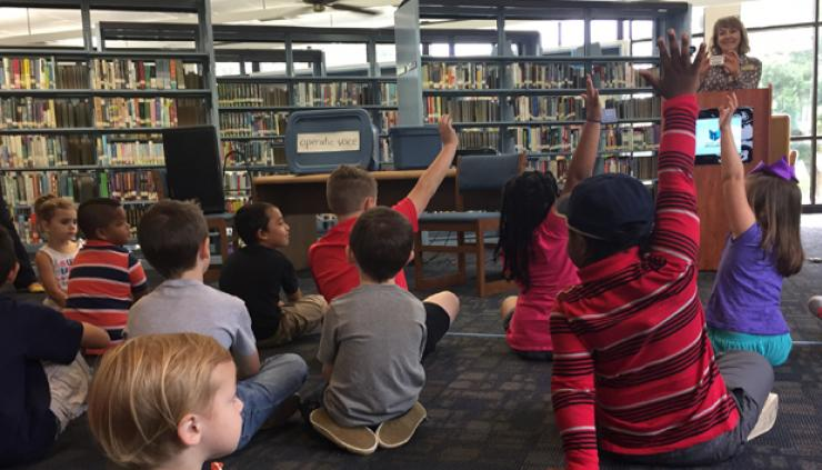 A group of children, who are seated on the floor of the Mary Vinson Memorial Library, raise their hands to answer a question posed by Georgia State Librarian Julie Walker, who is standing at a podium holding a library card.