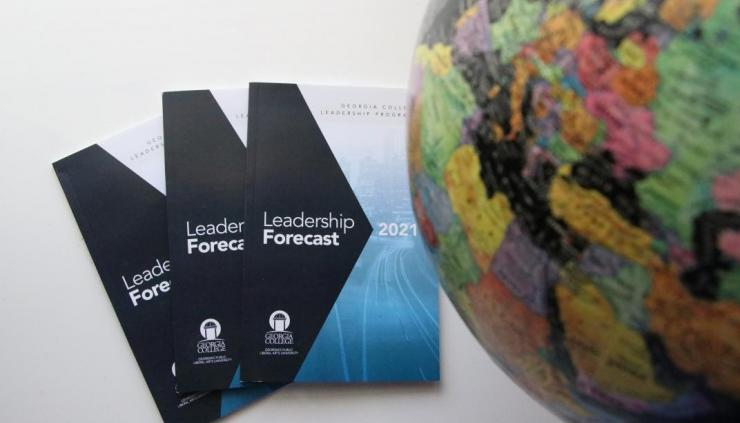 Image of the Inaugural Georgia College Leadership Forecast publication on a table along witha portion of a globe.