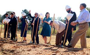 Georgia College President Steve Dorman, center, waves after breaking ground at the future site of the Andalusia Interpretive Center.