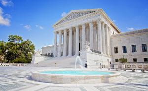The West Facade of the Supreme Court Building in Washington DC, shows the columned portico of the building with one of its two reflecting pools in the foreground.